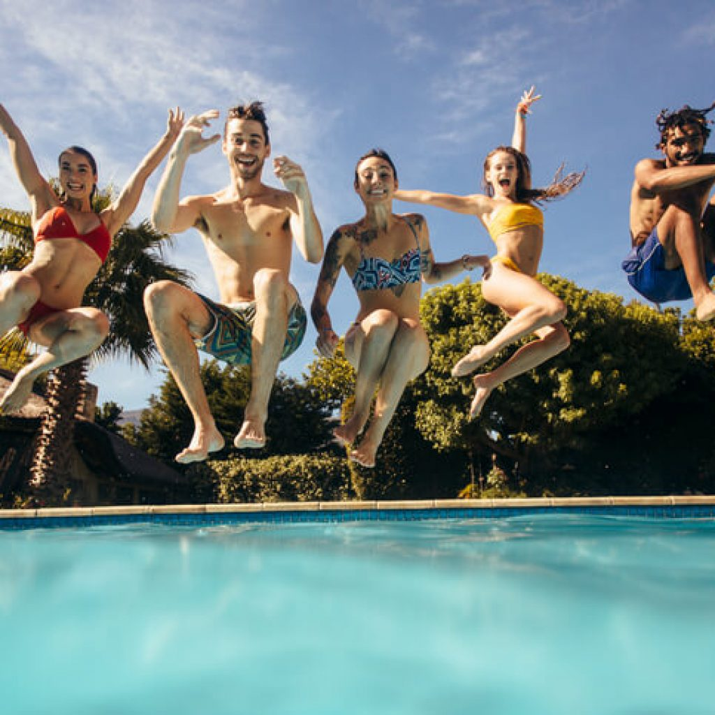 young people doing a cannonball into pool water safety month
