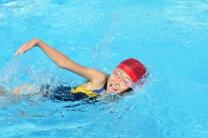 young girl with goggles and swimming cap doing a lap race