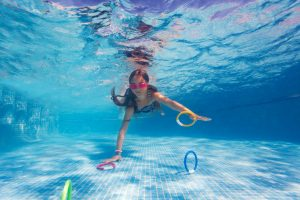 Child grabbing rings from the bottom of a swimming pool